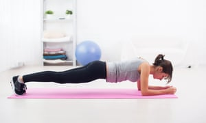 A woman planking in a gym