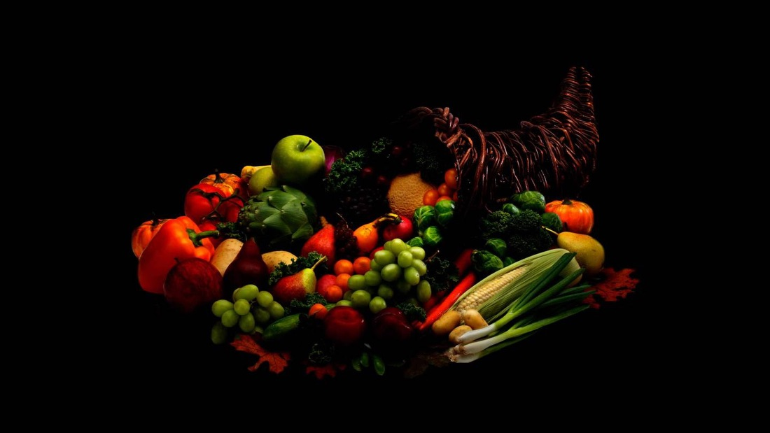 A cornucopia, a symbol of abundance, overflowing with fruit and vegetables.