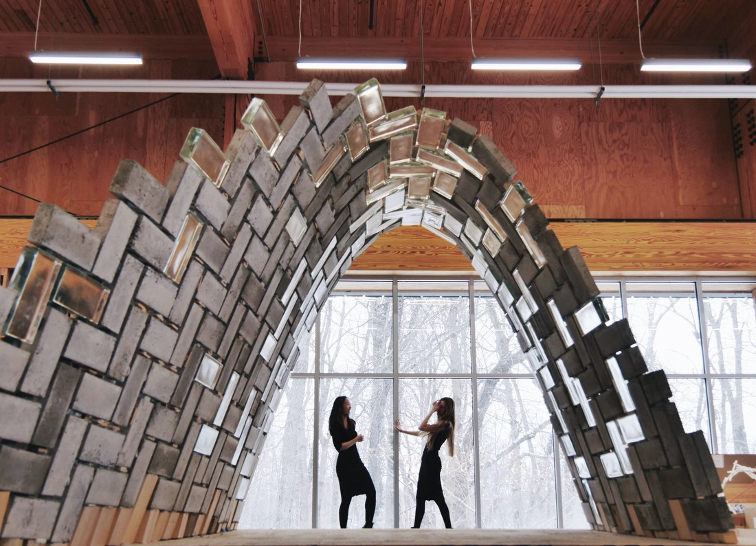 Professor Stefana Parascho and Isla Xi Han standing beneath a concrete and glass brick prototype built at the Embodied Computation Lab (ECL) in Princeton University's School of Architecture, in January 2020.